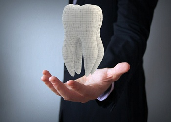 Man holding a tooth for dental insurance in Crown Point.