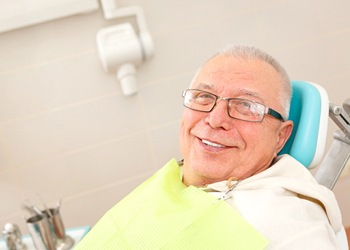 An older man smiling in the dentist's chair